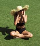 Frau in der Sonnenbrille und im schwarzen stilvollen Badeanzug des Hutes Lizenzfreie Stockfotografie