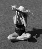 Frau in der Sonnenbrille und im schwarzen stilvollen Badeanzug des Hutes Stockfoto