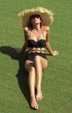 Frau in der Sonnenbrille und im schwarzen stilvollen Badeanzug des Hutes Lizenzfreie Stockfotos