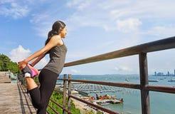 Frau in der Sportausstattung aufwärmend auf Pier nahe Wasser Stockfoto