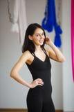 Frau in der sportiven Klage steht auf Hintergrund von hängenden Hängematten Stockfoto