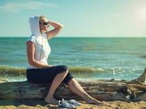 Frau in der Sportkleidung auf einem Klotz am Strand Stockbilder