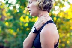 Frau in der Sportkleidung, die ihren Hals durch schmerzliche Verletzung, über a berührt stockfoto