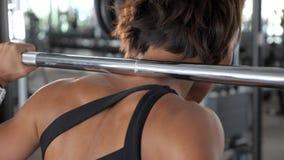 Frau in der Sportkleidung wird Hocken mit Barbell, hintere Ansicht tun stock video footage