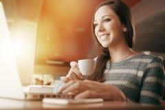 Frau an der Stange unter Verwendung eines Laptops Lizenzfreie Stockfotografie