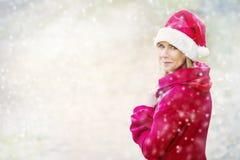 Frau in der stehenden Außenseite Sankt-Hutes im Schnee Stockbild
