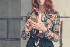 Frau in der Straße unter Verwendung ihres Telefons Stockfoto