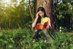 Frau in der Stresssituation, wenn ein Buch im Park gelesen wird lizenzfreies stockbild