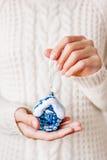 Frau in der Strickjacke, die eine Weihnachtsdekoration - blaues Haus hält Lizenzfreie Stockfotos