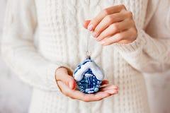 Frau in der Strickjacke, die eine Weihnachtsdekoration - blaues Haus hält Stockfotografie