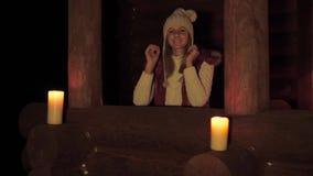 Frau in der Strickjacke geht in Richtung zum Portal des Hauses am Abend durch Kerzenlicht stock video