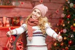 Frau in der Strickjacke mit den Daumen herauf nahen verzierten Weihnachtsbaum Lizenzfreies Stockfoto