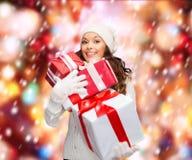 Frau in der Strickjacke und im Hut mit vielen Geschenkboxen Stockfoto