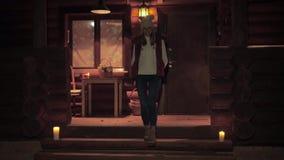 Frau in der Strickjacke und im Hut, steigt vom Portal, am Abend durch Kerzenlicht ab stock video