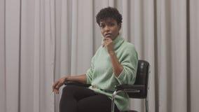 Frau in der tadellosen Strickjacke im Studio mit grauem Vorhanghintergrund, neunziger Jahre offise Art stock video