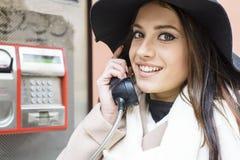 Frau an der Telefonzelle Stockbild