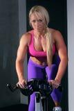 Frau an der Turnhalle auf einem Fahrrad Stockbild