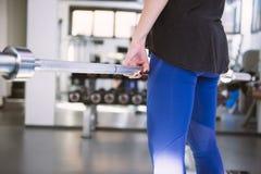 Frau in der Turnhalle trainierend mit Gewichten Lizenzfreies Stockbild