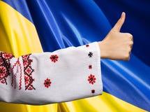 Frau in der ukrainischen Kleidung zeigt Symbol-O.K. gegen ukrainisches fla Stockfoto