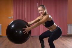 Frau in der untersetzten Position, die Eignungs-Ball hält stockfoto