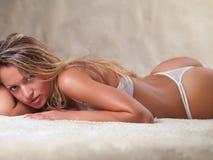 Frau in der Unterwäsche, die auf dem Teppich liegt Lizenzfreies Stockfoto