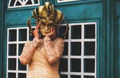 Frau in der venetianischen Maske nahe Gebäude Lizenzfreie Stockfotos