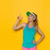 Frau in der vibrierenden Sport-Kleidung oben zeigend Lizenzfreie Stockfotografie