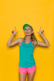 Frau in der vibrierenden Sport-Kleidung oben zeigend und aufpassend Stockfotografie