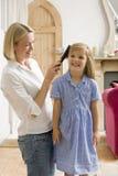 Frau in der vorderen Halle, die Haar des jungen Mädchens aufträgt Lizenzfreies Stockfoto