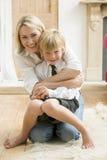 Frau in der vorderen Halle, die jungen Jungen und smili umarmt Stockbild