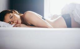 Frau in der Wäsche, die in ihrem Bett liegt Lizenzfreies Stockfoto