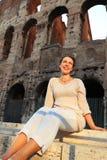 Frau in der weißen Abnutzung, die nahe Colosseum sitzt Stockbild