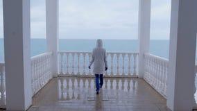 Frau in der weißen Jacke kam auf schöne Terrasse mit Seeansicht Rückseitige Ansicht stock footage