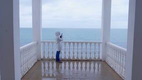 Frau in der weißen Jacke schießt Meereswellenvideo auf Smartphone auf schöner Terrasse mit Seeansicht Rückseitige Ansicht stock video