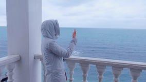 Frau in der weißen Jacke schießt Meereswellenvideo auf Smartphone auf schöner Terrasse mit Seeansicht Rückseitige Ansicht stock footage
