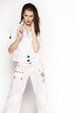 Frau in der weißen Jacke und in den Hosen Stockfotografie