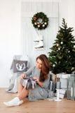 Frau in der Weihnachtsdekoration öffnet Kästen mit Geschenken unter dem Baum lizenzfreie stockfotografie