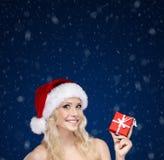 Frau in der Weihnachtskappe übergibt das Geschenk, das mit rotem Papier eingewickelt wird Stockfoto