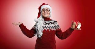 Frau in der Weihnachtsstrickjacke und in Sankt-Hut mit Geschenken Lizenzfreies Stockfoto