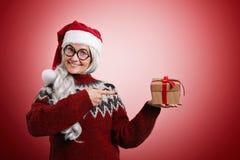 Frau in der Weihnachtsstrickjacke und in Sankt-Hut mit Geschenken Lizenzfreies Stockbild