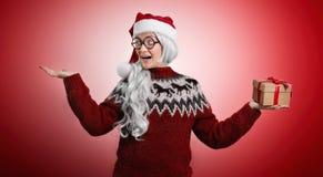 Frau in der Weihnachtsstrickjacke und in Sankt-Hut mit Geschenken Lizenzfreie Stockfotos
