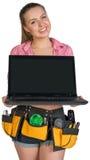 Frau in der Werkzeuggurtvertretung öffnete Laptop mit Stockbilder