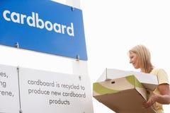 Frau an der Wiederverwertung der Mitte, die Pappe sich entledigt Lizenzfreies Stockfoto