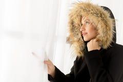Frau in der Winter-Kleidung, die heraus das Fenster schaut Lizenzfreie Stockfotografie