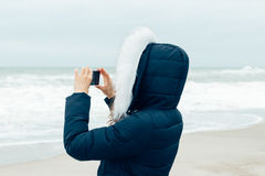 Frau in der Winterjacke mit Haube unter Verwendung eines Handys auf dem bea Lizenzfreie Stockfotografie