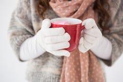 Frau in der Winterkleidung, die einen Becher hält Stockfotografie