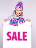 Frau in der Winteroberbekleidung hält die weiße Fahne mit Verkaufswort Lizenzfreies Stockfoto