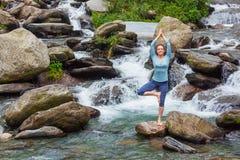 Frau in der Yoga asana Vrikshasana-Baumhaltung am Wasserfall draußen Stockbild