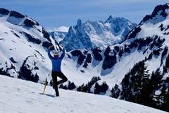 Frau in der Yoga-Haltung auf Schnee umfasste Gebirgsspitze mit schönen Ansichten Stockfotos