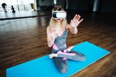 Frau in der Yogaklasse mit VR-Kopfhörer Lizenzfreie Stockfotos